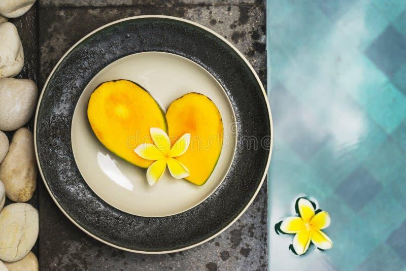 De twee helften van sappige verse mango op een plaat door de pool royalty-vrije stock fotografie