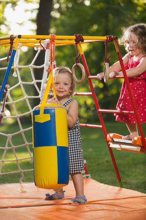 De twee kleine babymeisjes die bij openluchtspeelplaats spelen stock fotografie