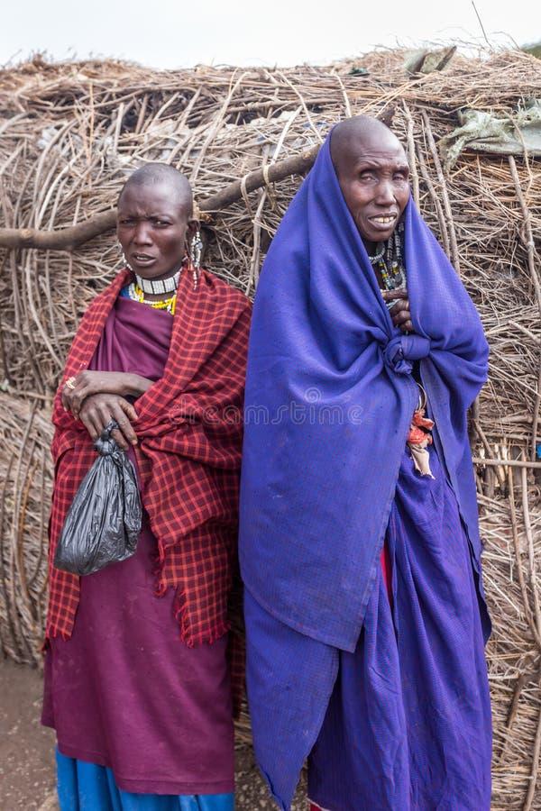 De twee Maasai-vrouwentribune dichtbij hun huis bekijkt mijn camera met het benieuwd zijn royalty-vrije stock foto's