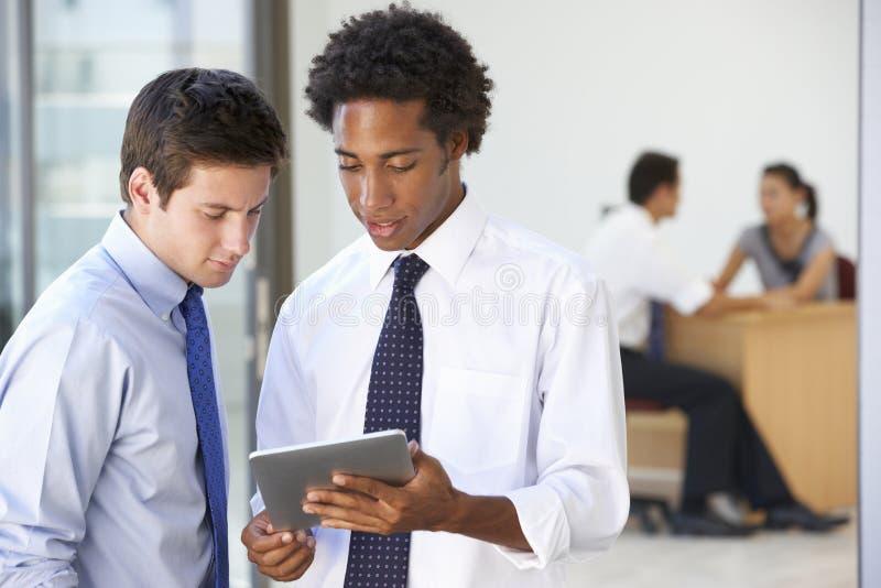De twee Mannelijke Uitvoerende macht die Tabletcomputer bekijken met Bureau Meeti stock fotografie