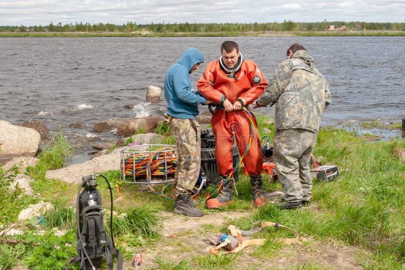 De twee medewerkershulp bereidt een professionele duiker voor het werk voor royalty-vrije stock afbeelding