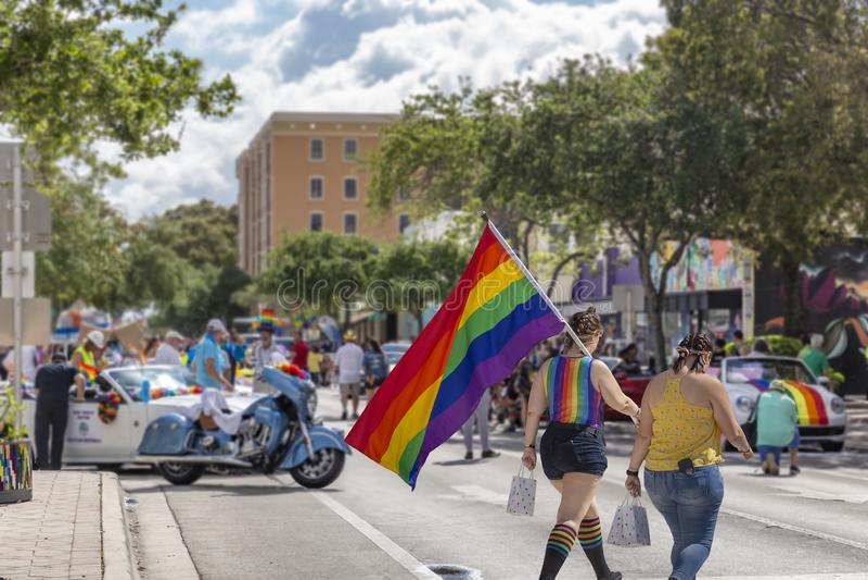 De twee meisjes lopen aan Pride Fest met een regenboogvlag stock afbeelding
