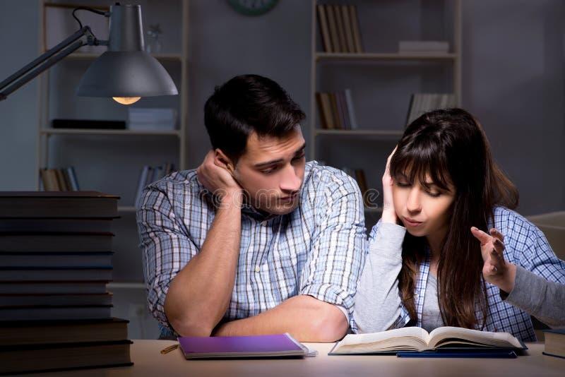 De twee studenten die laat bij nacht bestuderen royalty-vrije stock afbeelding