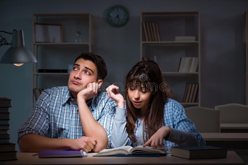 De twee studenten die laat bij nacht bestuderen royalty-vrije stock foto
