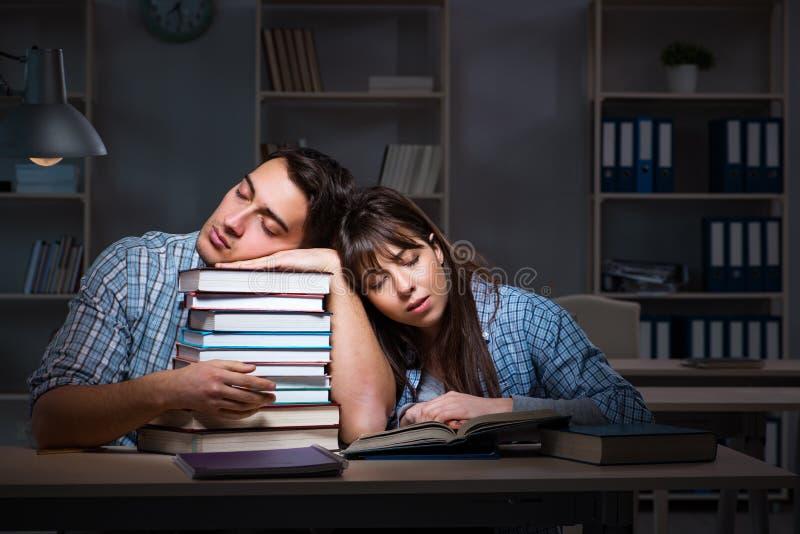 De twee studenten die laat bij nacht bestuderen stock foto