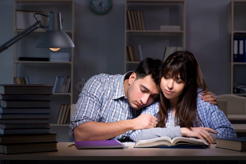 De twee studenten die laat bij nacht bestuderen stock foto's