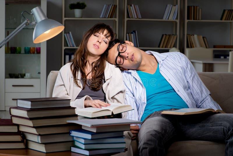 De twee studenten die laat het voorbereidingen treffen voor examens bestuderen royalty-vrije stock foto