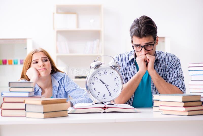 De twee studenten runnng uit tijd om voor examens voorbereidingen te treffen royalty-vrije stock foto's