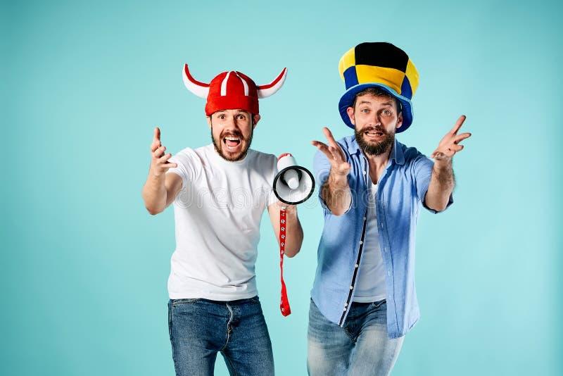 De twee voetbalventilators met mondstuk over blauw stock fotografie