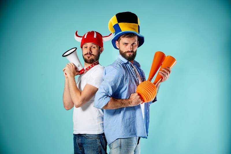 De twee voetbalventilators met mondstuk over blauw stock afbeelding