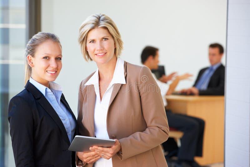De twee Vrouwelijke Uitvoerende macht die Tabletcomputer met Bureauvergadering met behulp van op Achtergrond royalty-vrije stock foto