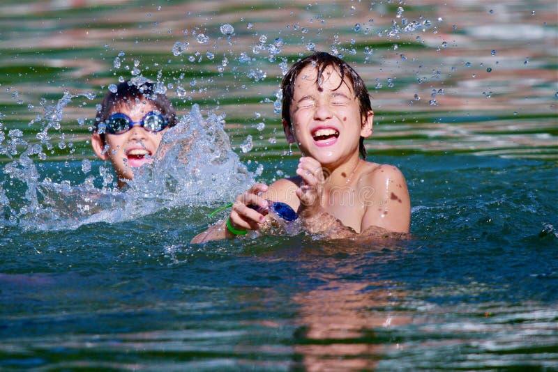 De tweeling jongens spelen in het water royalty-vrije stock foto's