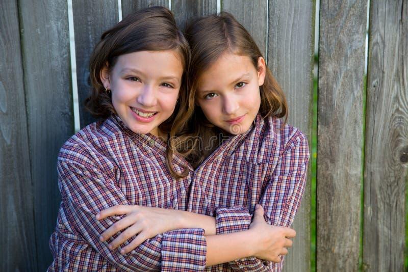 De tweelingmeisjes kleedden omhoog zich siamese met zijn vaderoverhemd stock afbeelding