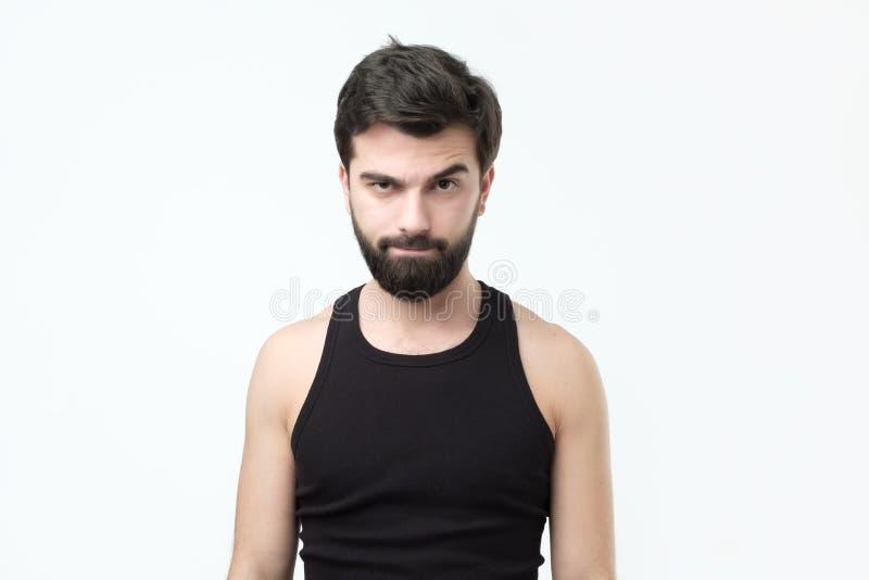 De twijfelachtige gebaarde jongelui bij de zwarte t-shirtmens hebt twijfelachtige uitdrukking op gezicht royalty-vrije stock fotografie