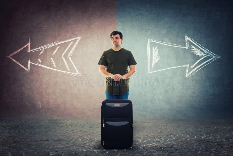De twijfelachtige mensenreiziger status achter zijn bagage moet zijn volgende vakantiebestemming kiezen stock fotografie