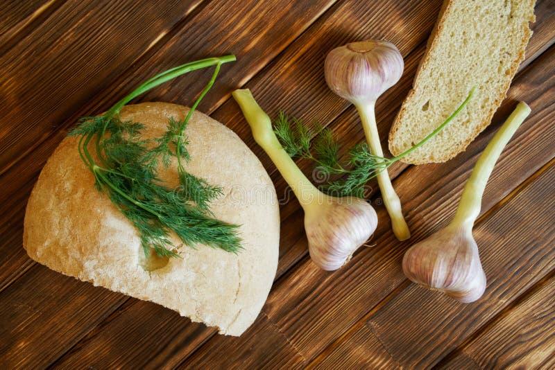 De twijgen van dille, knoflook en een brood van wit rond brood liggen op een rustieke houten die lijst van pijnboomraad wordt gem royalty-vrije stock foto's