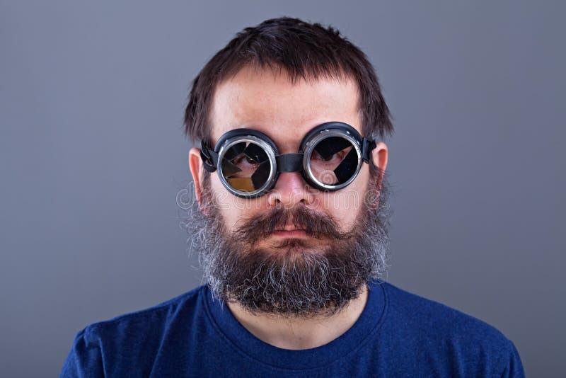 De type étrange avec les cheveux emmêlés et grande la barbe portant le weldin cassé photo libre de droits
