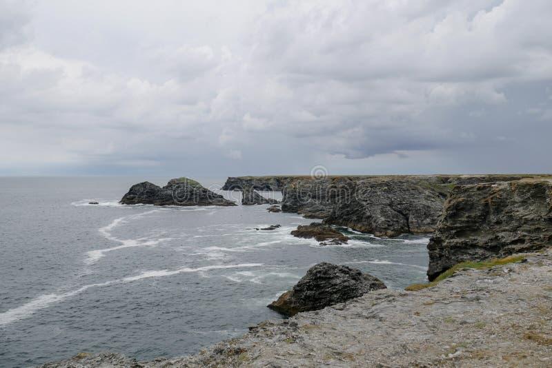De typische kustlijn van Bretagne met grijze bewolkte hemel en reusachtigheid van de Atlantische Oceaan stock afbeelding