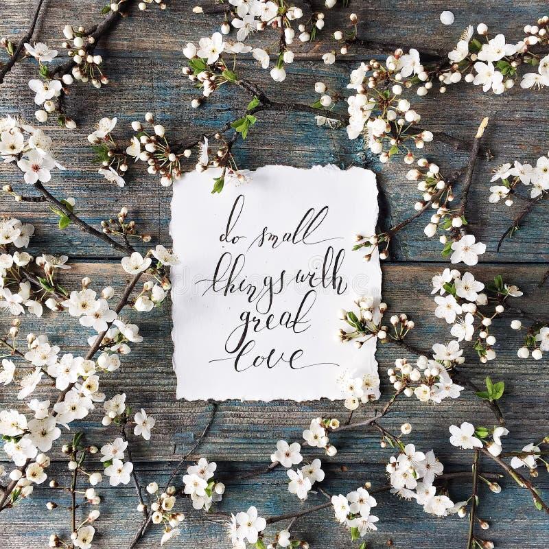 De uitdrukking ` doet kleine dingen met grote die liefde ` in kalligrafiestijl wordt geschreven op papier met kroonkader royalty-vrije stock fotografie