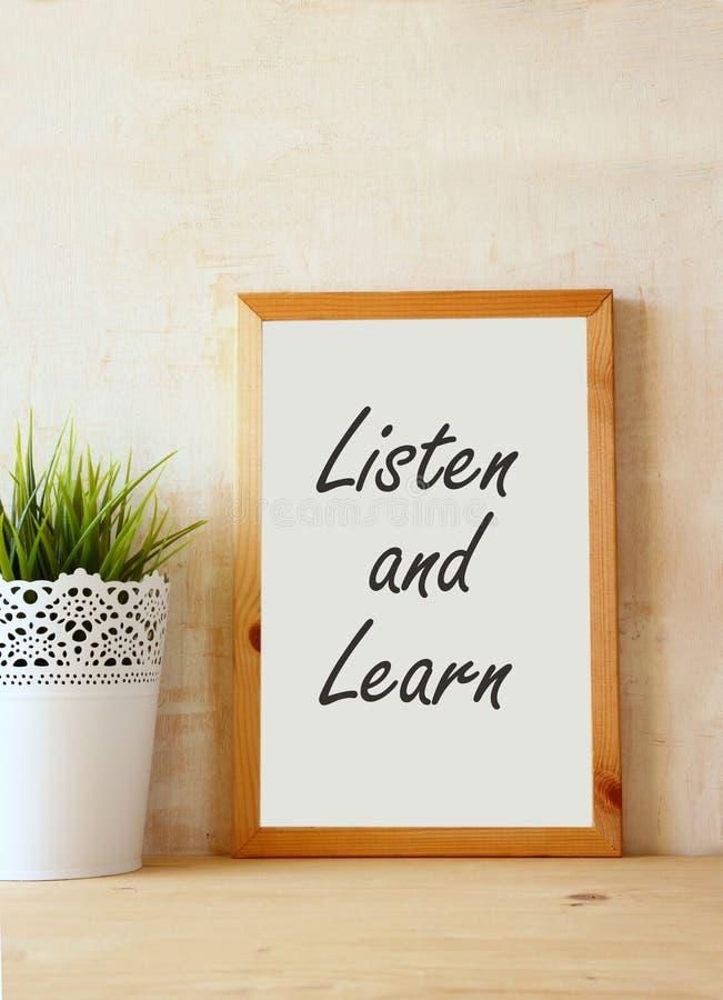 De uitdrukking luistert en leert geschreven over wit tekenbord tegen rustieke geweven muur stock fotografie