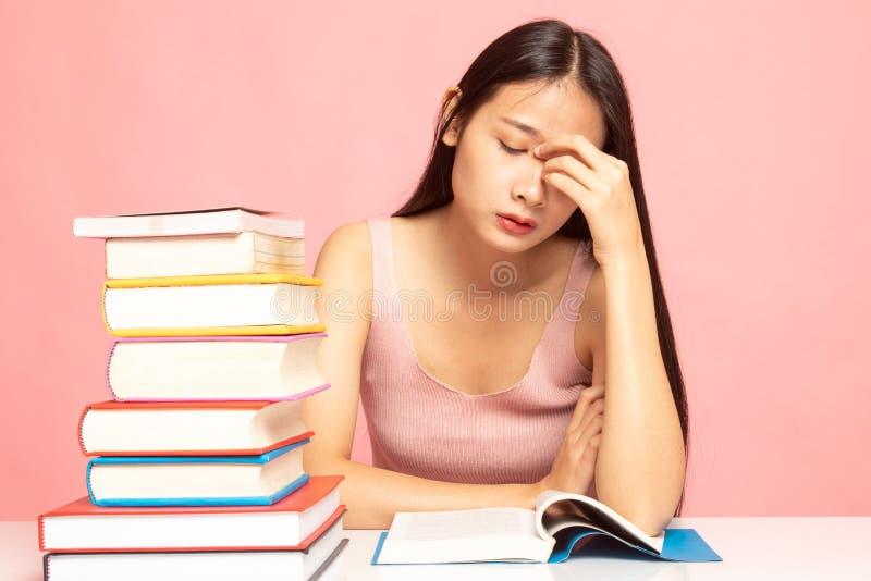 De uitgeputte Aziatische vrouw geworden hoofdpijn las een boek met boeken op lijst stock foto's