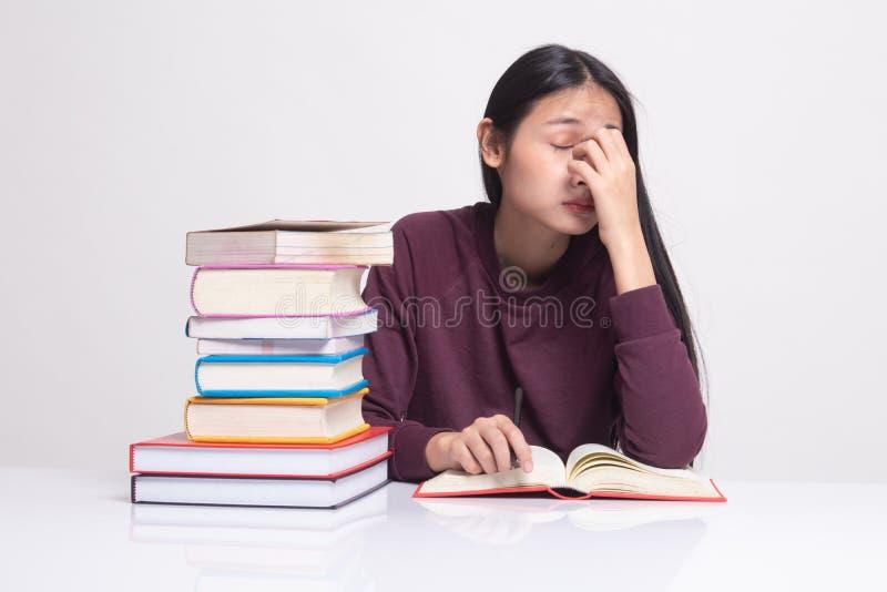 De uitgeputte Aziatische vrouw geworden hoofdpijn las een boek met boeken op lijst royalty-vrije stock afbeelding