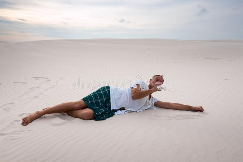 De uitgeputte mens ligt op het zand en drinkt de overblijfselen van water royalty-vrije stock foto