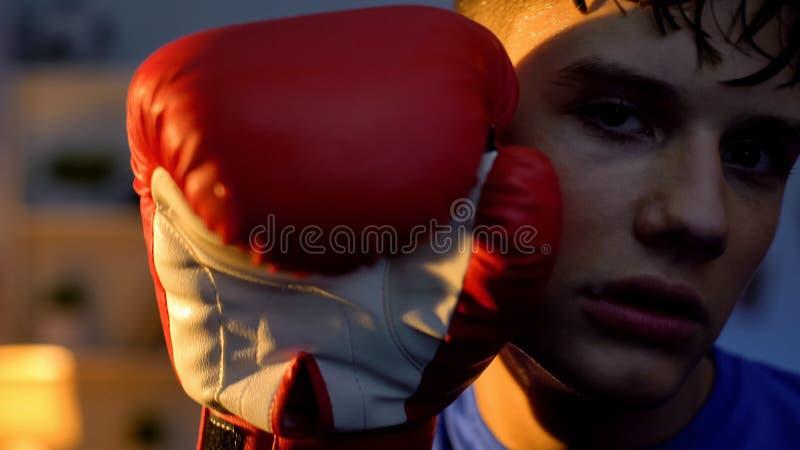 De uitgeputte tienerholding dient bokshandschoen dichtbij gezicht in onderzoekend camera royalty-vrije stock afbeelding