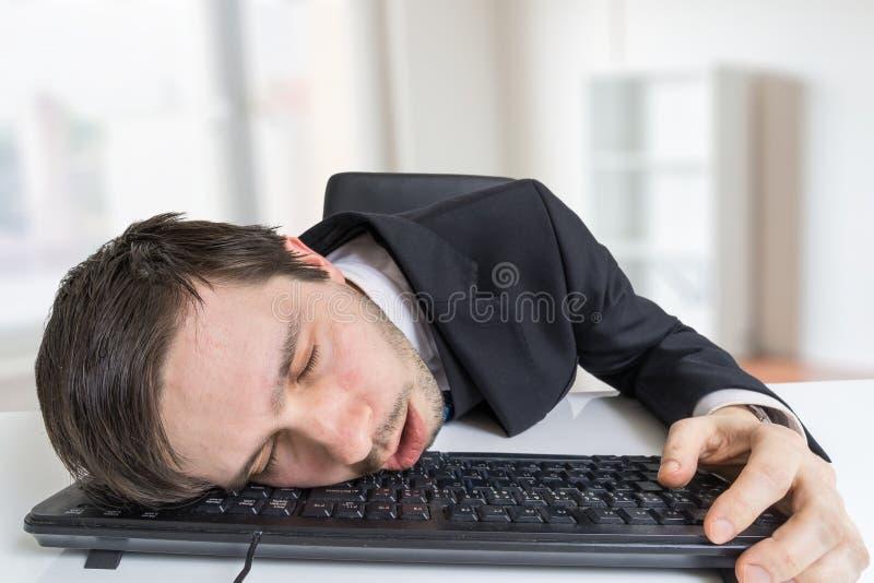 De uitgeputte of vermoeide zakenman slaapt op toetsenbord in bureau stock afbeeldingen