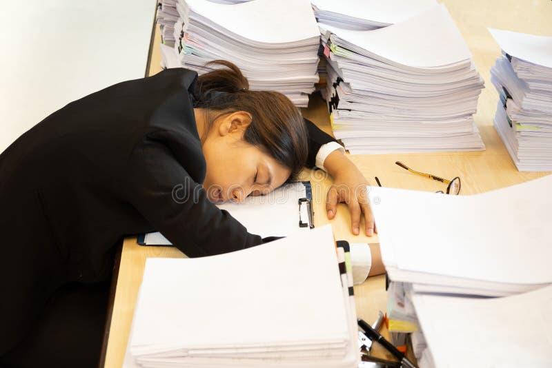 De uitgeputte vrouw heeft partij van het werk met documentendaling in slaap op werkend bureau stock afbeeldingen