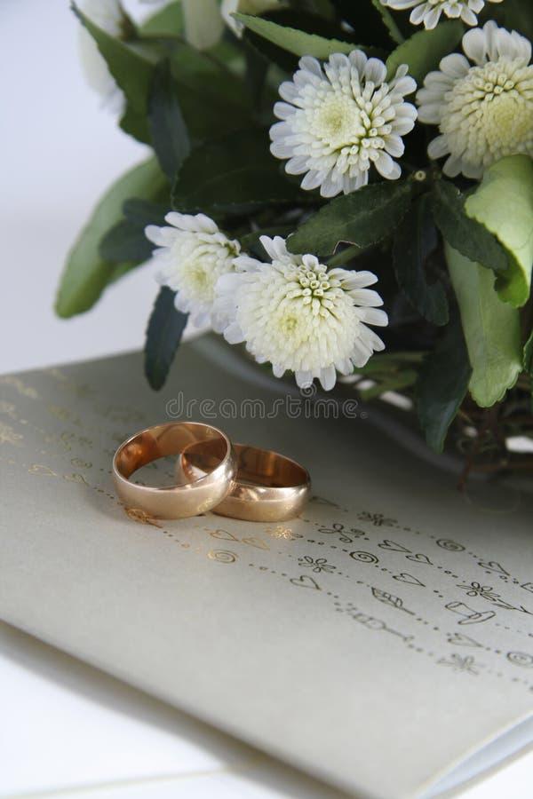 De uitnodiging van het huwelijk, gouden ringen en bloemen stock fotografie