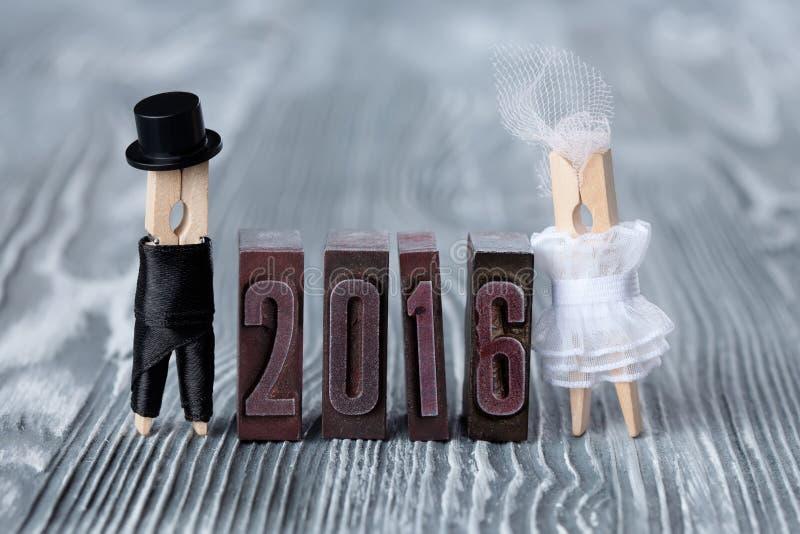 De uitnodiging van het huwelijk het jaar van 2016 Bruidegom in zwart kostuum en bruid in witte kleding clothespins royalty-vrije stock afbeelding