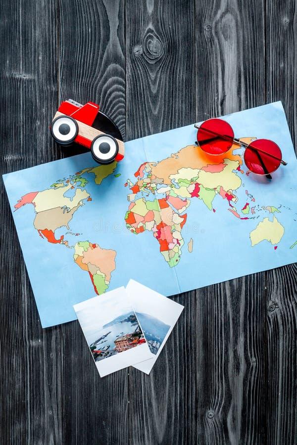 De uitrusting van het kinderentoerisme met kaart en de beelden op donkere vlakte als achtergrond lagen royalty-vrije stock foto