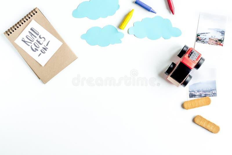 De uitrusting van het kinderentoerisme met speelgoed en de nota over witte vlakte als achtergrond leggen model royalty-vrije stock afbeelding