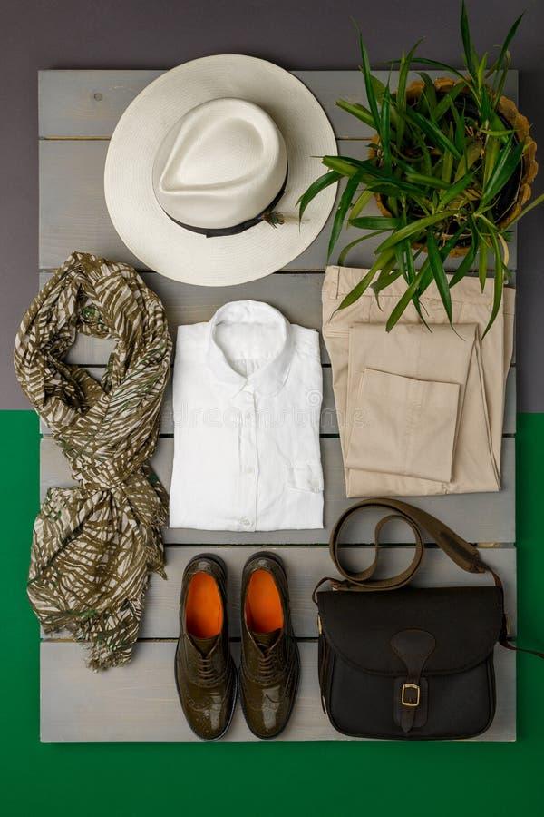 De uitrusting van vrouwen op houten achtergrond Manierkleren beige strohoed, beige broek, wit overhemd, groene sjaalzwarte stock foto's