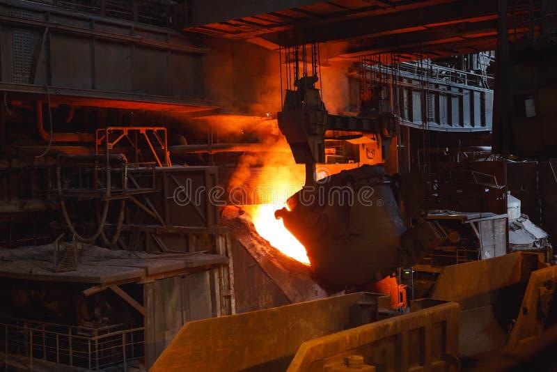 De uitsmelting van het metaal in de gieterij, Fabrieksarbeider neemt een steekproef voor metaal stock fotografie