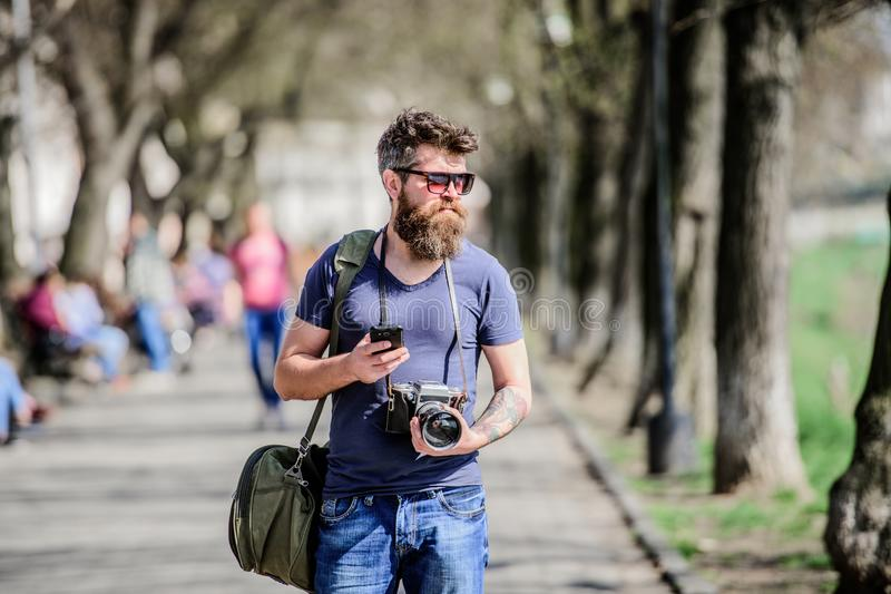De uitstekende camera van de fotograafgreep Moderne blogger Handmontages Fotograaf met baard en snor Toerist stock foto