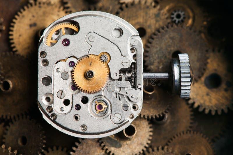 De uitstekende delen van het uurwerkmechanisme en de macromening van het handhorloge roestige de toestellenachtergrond van het gr stock foto