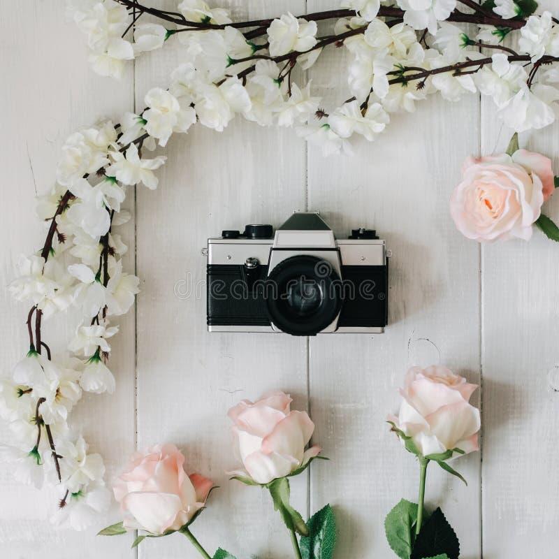 De uitstekende filmcamera in het midden, roze sakuratak, nam bloemen op het witte houten bureau toe De hoogste vlakke mening, leg stock foto's