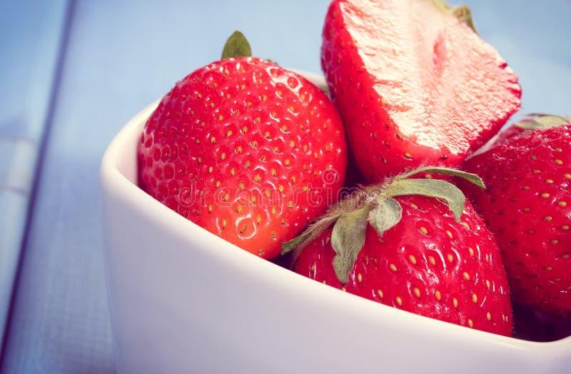 De uitstekende foto, Verse rijpe aardbeien in glas werpt op raad, gezond dessert royalty-vrije stock afbeeldingen