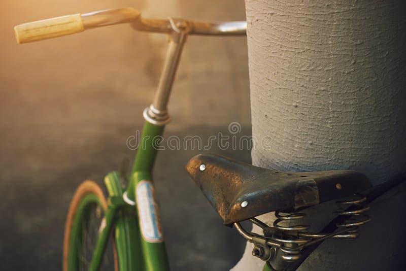 De uitstekende groene fiets met een oud zadel is in bijlage aan de pijp stock afbeelding