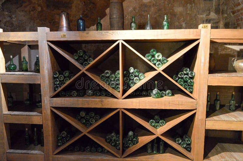 De uitstekende groene lege wijn en bierglasflessen in een wijnkast met planken in oude middeleeuws bricked steenkelder royalty-vrije stock foto