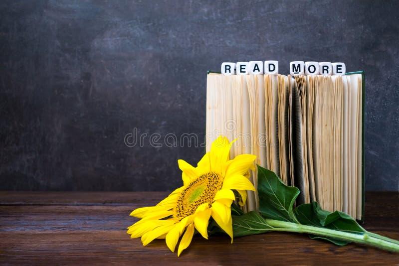 De uitstekende Oude boeken met woorden LEZEN MEER en zonnebloem Open Boek stock foto
