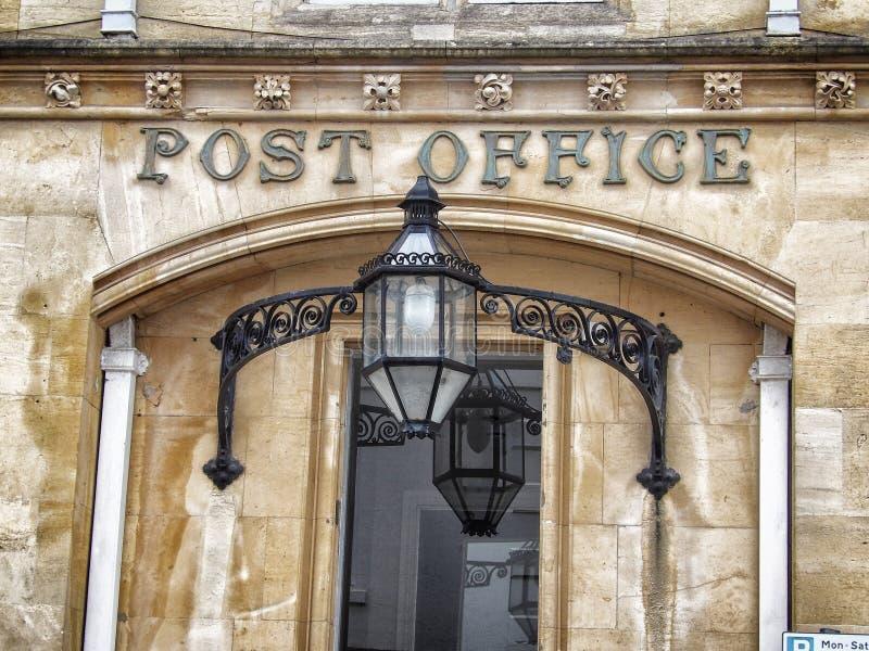 De uitstekende oude postkantoorbouw met teken op ingang stock foto's
