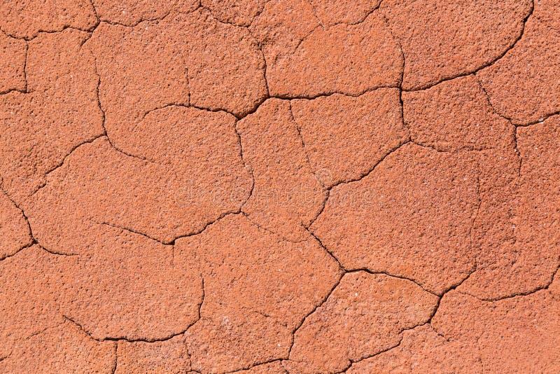 De uitstekende roodachtige of oranje gebarsten achtergrond van de rotstextuur Abstracte steentextuur stock afbeeldingen
