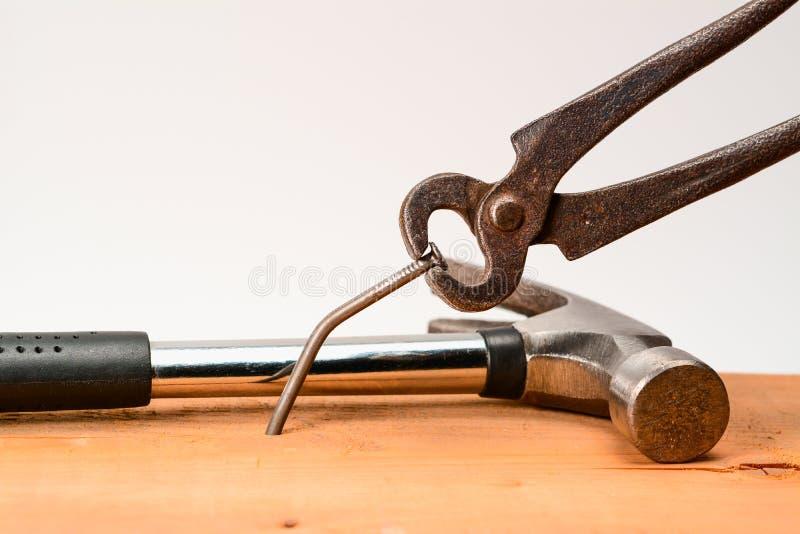 De uitstekende ruwe gesmede tang trekt een grote die spijker van de raad wordt gebogen Met hamer op achtergrond royalty-vrije stock afbeeldingen