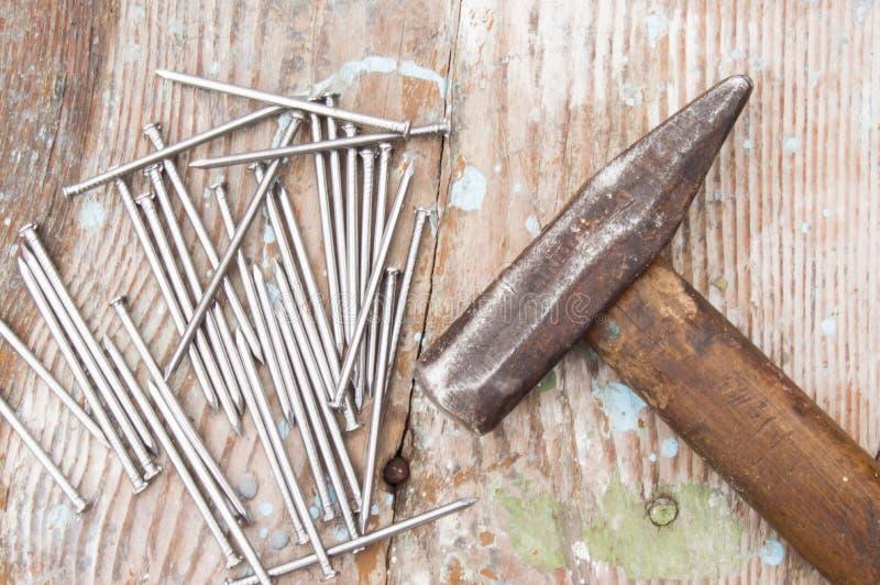 De uitstekende schrijnwerkershamer en de spijkersschoenspijkers die op oude houten lijst of werkbank met plonsen liggen schildere royalty-vrije stock afbeelding