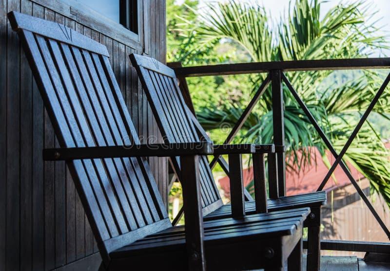 De uitstekende stijl houten stoel op balkon in zon glanst stock fotografie