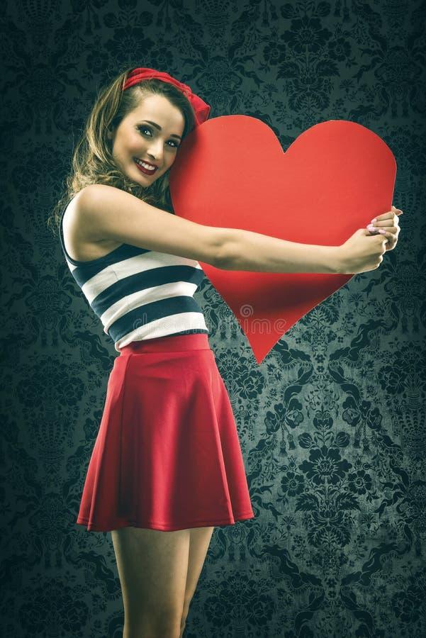 De uitstekende vrouw in rode kleding omhelste groot document hart royalty-vrije stock fotografie