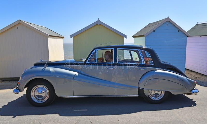 De uitstekende Zilveren en Zwarte Auto van Armstrong Siddeley die voor strandhutten wordt geparkeerd royalty-vrije stock afbeeldingen
